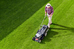 Mowing senior man in the garden royalty free stock photography