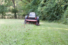 Mowing the yard. Zero turn mower half mowed green grass royalty free stock photography