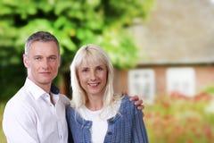 Moyen Âge heureux de couples devant une maison Image stock