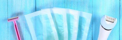 Moyens pour l'épilation Epilator, rasoir pour raser, bandes de cire sur une feuille tropicale sur un fond en bois bleu Epilation, photographie stock