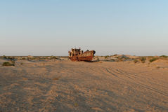 Moynaq rusty fishing boat. Rusty ship lying in the sand at the former Soviet Aral Sea port of Moynaq in Uzbekistan Royalty Free Stock Photos