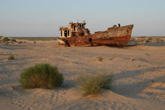 Moynaq ship wreckage. Rusty ship lying in the sand at the former Soviet Aral Sea port of Moynaq in Uzbekistan Royalty Free Stock Image