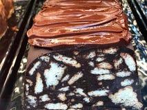 Mozaïekchocolade en Koekjescake met Romige Chocoladesaus Sluit omhoog Macroweergeven bij Showcase van Patisserie royalty-vrije stock foto