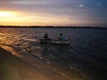 Mozambicaanse visser op weg naar huis in de boot van hun visser stock fotografie