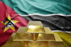 Mozambican gold reserves. Shining golden bullions on the mozambican flag background Stock Photo