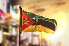 Mozambique Flag Against City Blurred Background At Sunrise Backl. Ight Sky Royalty Free Stock Image