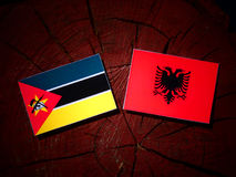 Mozambique flag with Albanian flag on a tree stump isolated. Mozambique flag with Albanian flag on a tree stump Royalty Free Stock Photography