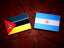 Mozambique flag with Argentinian flag on a tree stump isolated. Mozambique flag with Argentinian flag on a tree stump Stock Photography