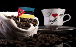 Mozambique flag in a bag with coffee beans  on black. Background Stock Photos