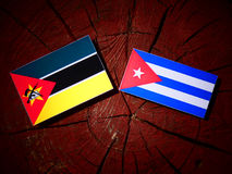 Mozambique flag with Cuban flag on a tree stump isolated. Mozambique flag with Cuban flag on a tree stump Stock Photos
