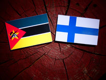 Mozambique flag with Finnish flag on a tree stump isolated. Mozambique flag with Finnish flag on a tree stump Stock Photo