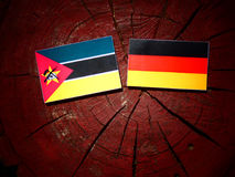 Mozambique flag with German flag on a tree stump isolated. Mozambique flag with German flag on a tree stump Stock Photos