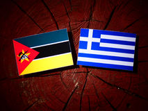Mozambique flag with Greek flag on a tree stump isolated. Mozambique flag with Greek flag on a tree stump Royalty Free Stock Photo