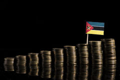 Mozambique flag with lot of coins  on black. Background Stock Photos