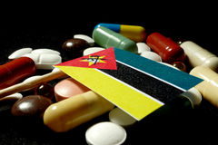 Mozambique flag with lot of medical pills isolated on black back Royalty Free Stock Images
