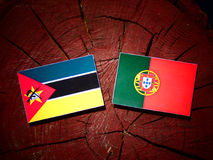 Mozambique flag with Portuguese flag on a tree stump isolated. Mozambique flag with Portuguese flag on a tree stump Stock Images