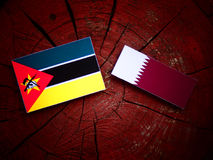 Mozambique flag with Qatari flag on a tree stump isolated. Mozambique flag with Qatari flag on a tree stump Stock Photo