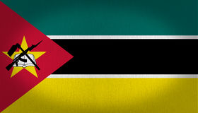 Mozambique Flag. With a red left side triangle with a yellow star and a book, over it a rifle and a seeding tool, in the back has three lines, one in dark green Royalty Free Stock Images