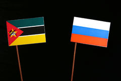 Mozambique flag with Russian flag isolated on black. Background Stock Image