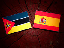 Mozambique flag with Spanish flag on a tree stump. Mozambique flag with Spanish flag on a tree stump Stock Photos