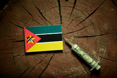 Mozambique flag on a stump with syringe injecting money. In flag Royalty Free Stock Images