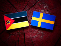 Mozambique flag with Swedish flag on a tree stump. Mozambique flag with Swedish flag on a tree stump Stock Photo