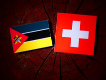 Mozambique flag with Swiss flag on a tree stump. Mozambique flag with Swiss flag on a tree stump Stock Image