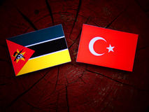 Mozambique flag with Turkish flag on a tree stump isolated. Mozambique flag with Turkish flag on a tree stump Stock Image