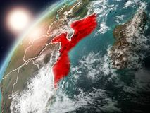 Mozambique on planet Earth in sunset. Mozambique during sunset highlighted in red on planet Earth with clouds and visible country borders. 3D illustration Stock Photos