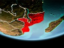 Mozambique in red in the evening. Country of Mozambique in red on planet Earth in the evening with visible border lines and city lights. 3D illustration Royalty Free Stock Photo