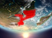 Mozambique with sun. Mozambique during sunrise highlighted in red on planet Earth with clouds. 3D illustration. Elements of this image furnished by NASA Royalty Free Stock Photos