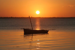 Mozambique Sunset. The sun sets over the African continent and over a fisherman Dhow Boat. Taken at Ilha Mocambique (Mozambique Island), Mozambique Stock Image