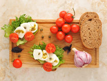 Mozarella with tomatoes on a wooden Board Royalty Free Stock Photo
