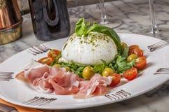 Mozarella und Parmaschinken, der von einem Salat mit Rakete begleitet wird, verlassen Lizenzfreie Stockfotografie