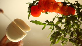 Mozzarella, arugula and tomatoes - sliced for salad. hands closeup stock video