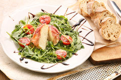 Mozzarella baked in ham of Parma with arugula Stock Photo
