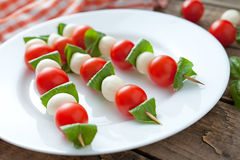 Mozzarella basil and tomatoes skewers on wooden. Sticks called caprese salad natural organic antipasti snack. Rustic style and natural light Royalty Free Stock Photo