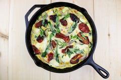 Mozzarella, Basilikum u. Zucchini Frittata in Roheisen lizenzfreie stockfotos