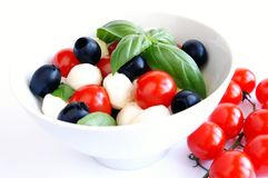 Mozzarella, black olives and tomato salad. Mozzarella boconccini cheese balls with cherry tomatoes, black olives and green fresh basil in a salad bowl on white Royalty Free Stock Photo