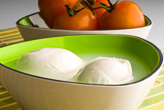 Mozzarella cheese. Cheese mozzarella in bowl and tomatoes in the background royalty free stock photos