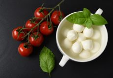 Mozzarella cheese, basil and tomatoes cherry on a gray background italian food, top view stock photography