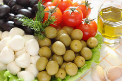 Mozzarella cheese, black and green olives, cherry tomatoes are o Royalty Free Stock Images