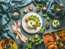 Mozzarella cheese in bowl with olives oil, green tomatoes and basil leaves on white plate , top view. Summer or Italian food still stock image
