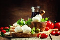 Mozzarella cheese, bread, olives and tomatoes, snack plate. Vintage wooden background, selective focus royalty free stock photo