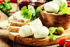 Mozzarella cheese, bread, olives and tomatoes, snack plate. Vintage wooden background, selective focus stock images