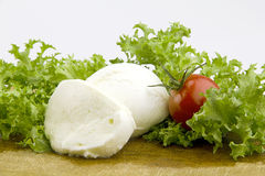 Mozzarella. Cheese on cutting board with lettuce and tomato Royalty Free Stock Photos