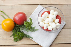 Mozzarella cheese in a glass bowl, tomatoes, sliced tomatoes and herbs on a wooden table Stock Photo