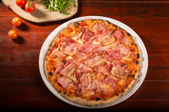 Mozzarella cheese and ham with bacon pizza. Delicious pizza with mozzarella cheese, arugula, ham, bacon, tomatoes on wooden paddle royalty free stock image