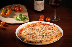 Mozzarella cheese pizza with mushrooms and arugula. Delicious pizza with mozzarella cheese, arugula, mushrooms and tomatoes on wooden paddle next to a glass of stock images