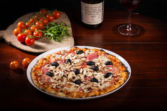 Mozzarella cheese pizza with mushrooms and olives. Delicious pizza with mozzarella cheese, arugula, mushrooms and tomatoes on wooden paddle next to a bottle of Stock Photography